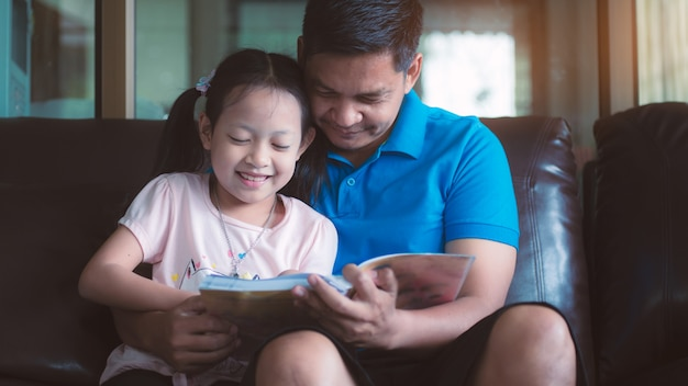 Asian father and his daughter reading a book at home Premium Photo