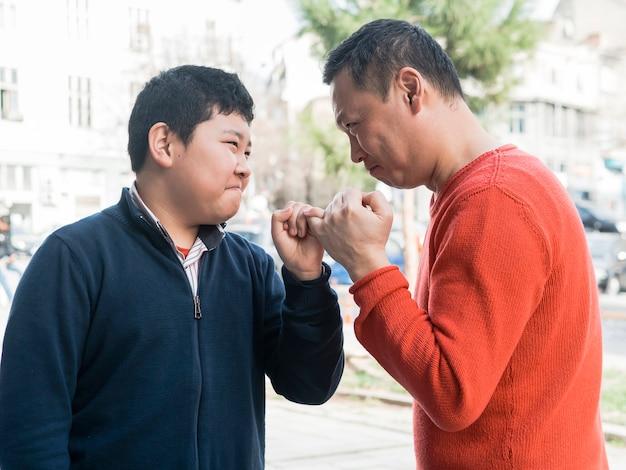 Padre e figlio asiatici che fanno una promessa Foto Gratuite