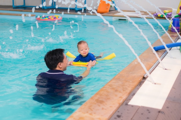 Asian father take cute little asian 18 months / 1 year old toddler baby child to swimming class Premium Photo