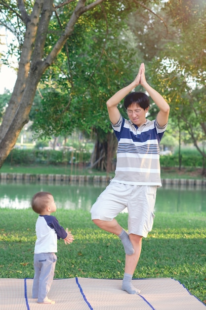 Asian father with eyes closed and 1 year old toddler boy child practices yoga & meditating outdoors on nature in summer, healthy lifestyle concept Premium Photo