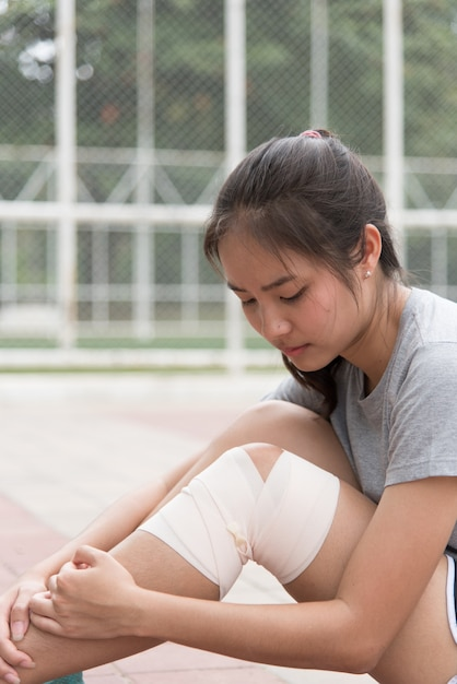 Asian female athlete sitting beside the stadium. she had a knee injury and got her first aid. Premium Photo