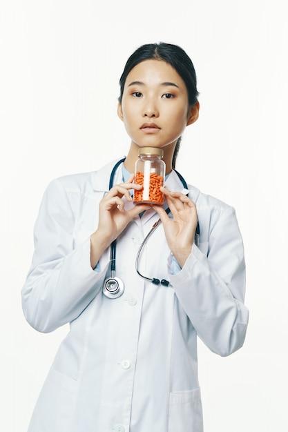 Азиатский женский доктор с оранжевыми таблетками Premium Фотографии