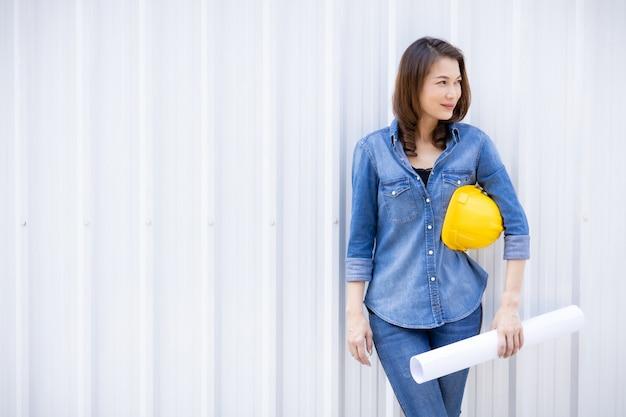 노란 모자와 아시아 여성 엔지니어입니다. 프리미엄 사진