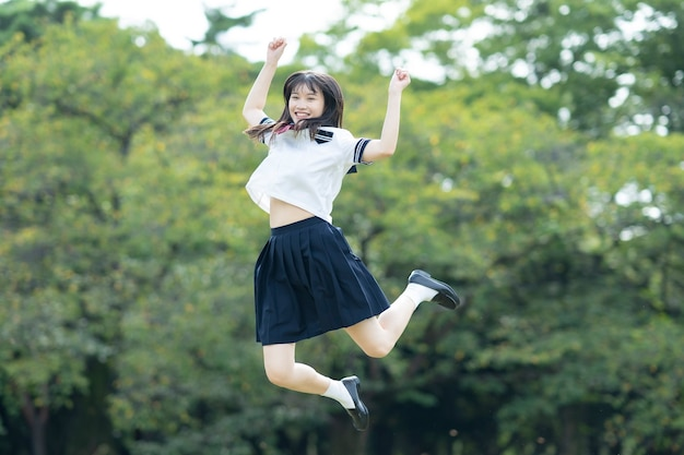 Asian female high school student frolicking with a smile in the park Premium Photo