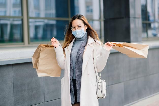 コート、眼鏡、医療用マスクを身に着けたアジア人女性が、荷物を手に持って通りに立っています。 Premium写真