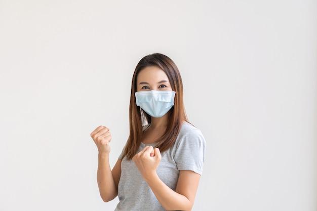 拳で手を上げて、幸せで叫んで白い背景の上のフェイスマスクのアジアの女性。 Premium写真
