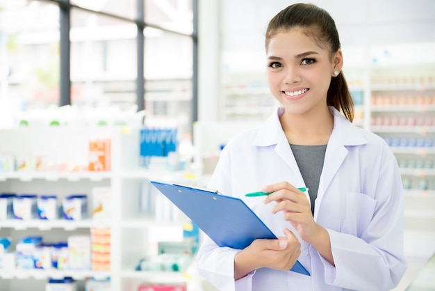 Asian female pharmacist working in chemist shop or pharmacy Premium Photo