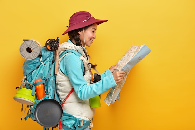Asian female tourist studies map, finds new destination to explore, travels alone, wears cap and active wear, carries big rucksack Free Photo