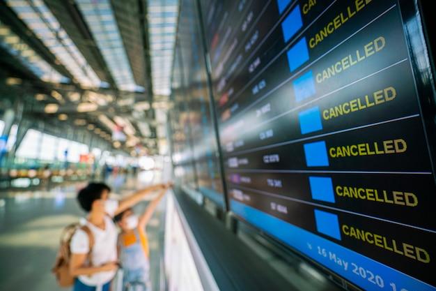 Азиатская путешественница смотрит на информационное табло рейсов в аэропорту Premium Фотографии