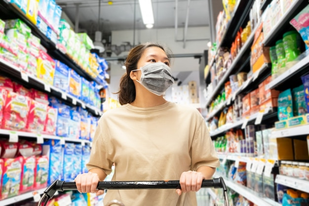 Asian female wearing protective face mask with shopping cart at ...