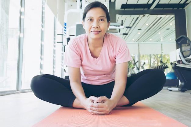 체육관에서 운동을하기 전에 워밍업 아시아 피트 니스 여자, 중년 여성 요가 운동 프리미엄 사진
