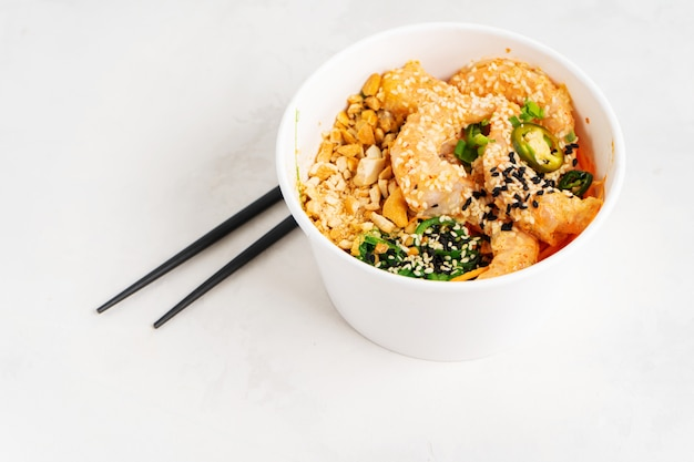 Азиатская предпосылка еды с пряным шаром poke креветки с рисом, морскими водорослями и семенами сезама, авокадоом в коробке для завтрака с палочками для еды на белизне. здоровый обед из морепродуктов. диетическое питание. вид сверху с копией пространства. Premium Фотографии
