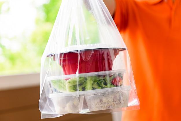 オレンジ色の制服を着た配達員が自宅で顧客に宅配したビニール袋に入ったアジアンフードボックス Premium写真