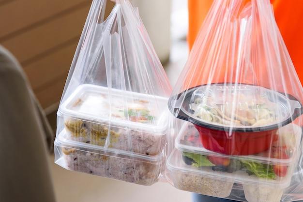 宅配業者が自宅に宅配したビニール袋入りのアジアンフードボックス Premium写真