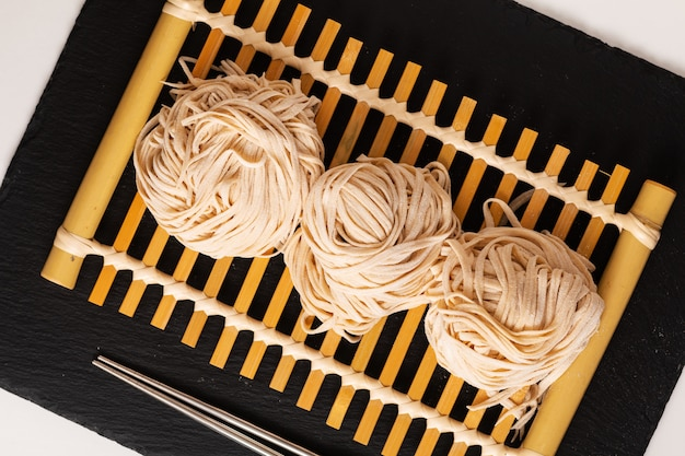 Asian food homemade oriental egg noodles on bamboo tray Premium Photo