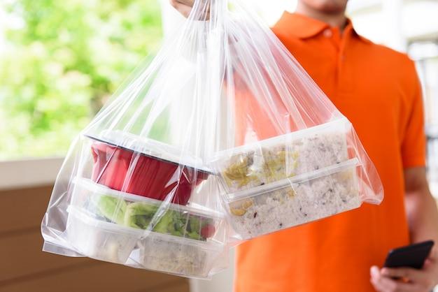 オレンジ色の制服を着た配達員が自宅の顧客に宅配ボックスで配達するアジア料理 Premium写真