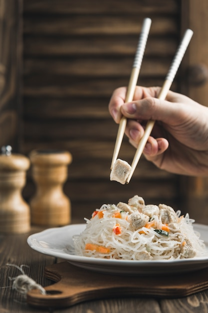 Asian Food Noodles Funchoza With Chicken And Sticks For Food On Wood