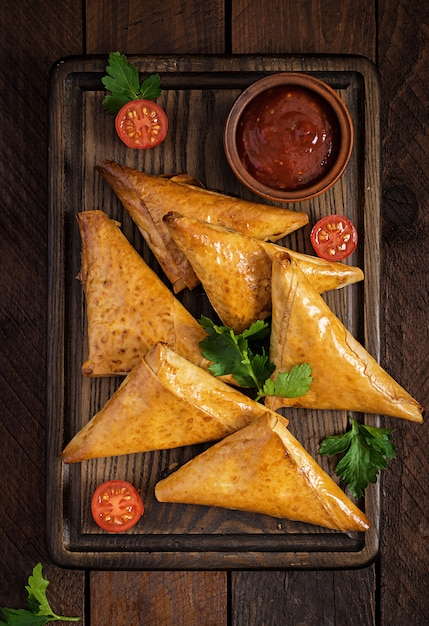 Asian food. samsa (samosas) with chicken fillet and cheese on wooden. Premium Photo