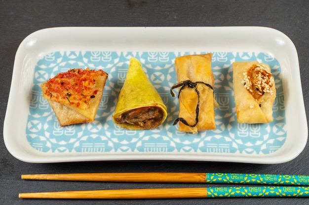 Asian food selection.duck cones,parcels,baskets with ginger and soy sauce,tikka crackers, windmills Premium Photo
