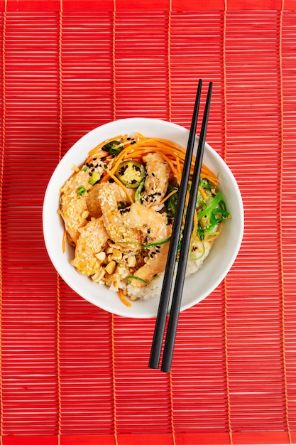 Asian food. teapot and cup, spicy shrimp poke bowl with rice, seaweeds and sesame seeds, avocado on red bamboo mat background with chopsticks over the red bamboo background. Premium Photo