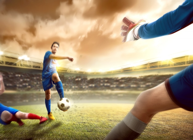 Asian football player man sliding tackle the ball from his opponent before him kicking the ball to the goal Premium Photo