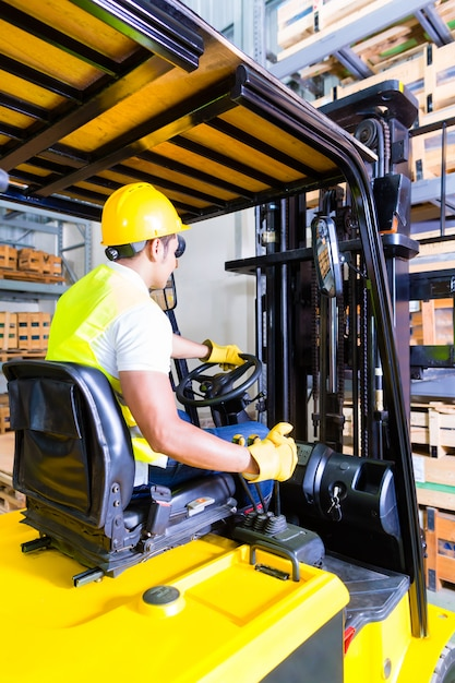 Asian fork lift truck driver lifting pallet in storage Premium Photo