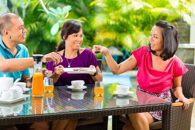 Asian friends having coffee on home porch Premium Photo