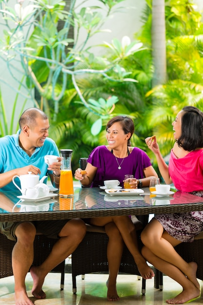 Asian friends having coffee on home porch Premium Photo