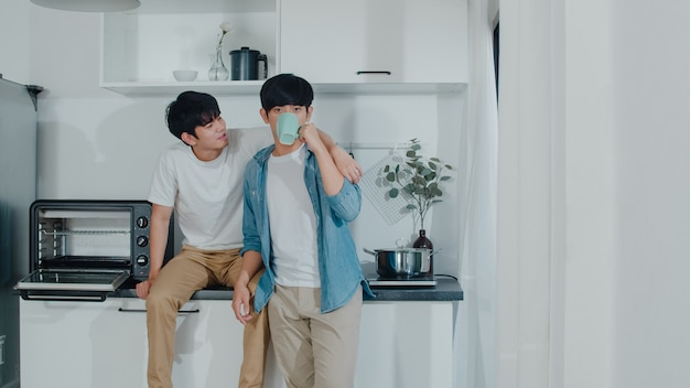 Asian gay couple drinking coffee, having a great time at home. young handsome lgbtq+ men talking happy relax rest together spend romantic time in modern kitchen at house in the morning . Free Photo