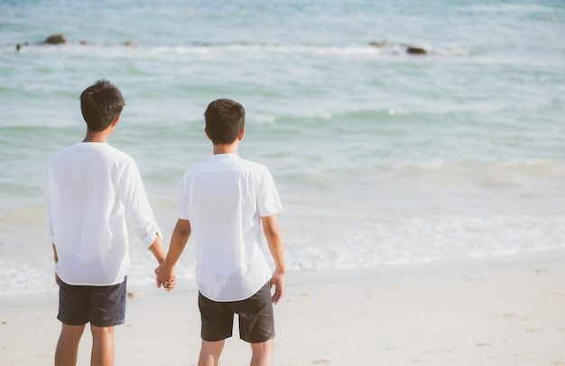 Asian gay couple holding hands together on the beach. Premium Photo