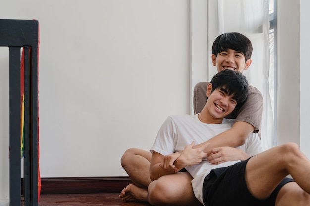 Asian gay couple lying and hugging on the floor at home. young asian lgbtq+ men kissing happy relax rest together spend romantic time in living room with rainbow flag at modern house in the morning. Free Photo