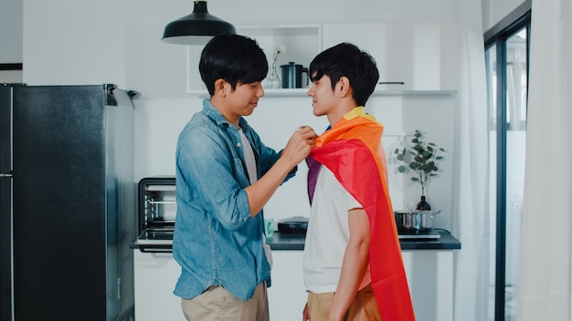 Asian gay couple standing and hugging room at home. young handsome lgbtq+ men kissing happy relax rest together spend romantic time in modern kitchen with rainbow flag at house in the morning . Free Photo