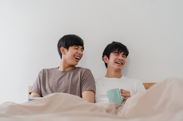 Asian gay men couple talking having a great time at modern home. young asia lover male happy relax rest drink coffee after wake up while lying on bed in bedroom at house in the morning . Free Photo