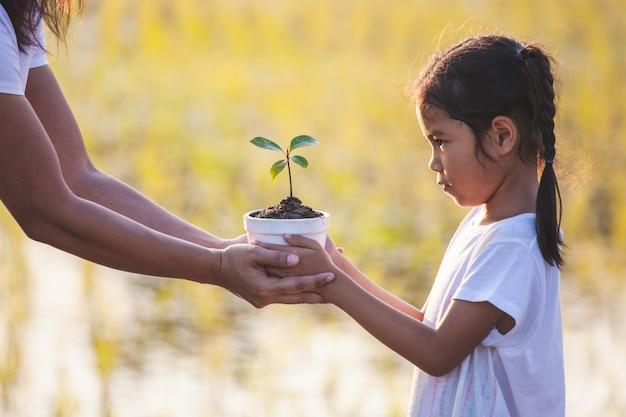 アジアの女の子と彼女の母親が地面に植栽を準備するための植木鉢に若い苗を保持 Premium写真