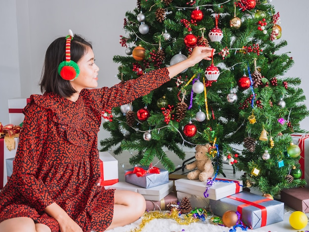 Asian girl celebrating christmas in house,woman decorate the christmas tree Premium Photo