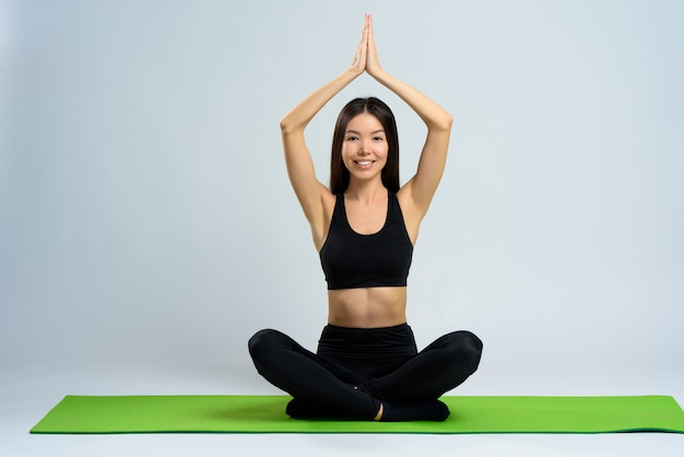 Asian girl does yoga on gym carpet. lotus pose. | Premium Photo