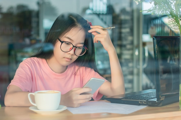 Asian girl in glasses stressed work with laptop and mobile phone in coffee shop or cafe Premium Photo