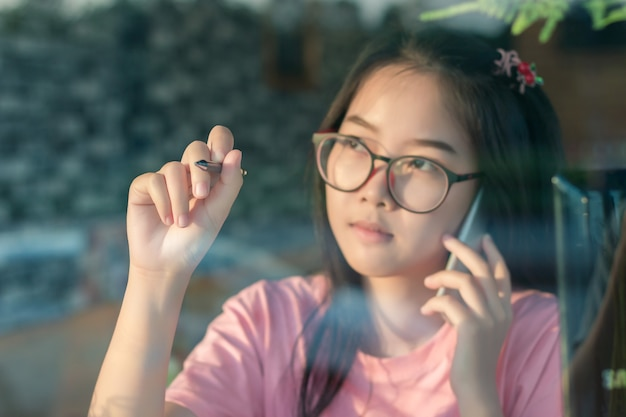 8cc6d4e3227 Asian girl in glasses talking on mobile phone and writing on the ...
