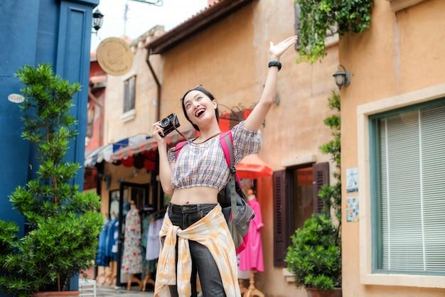 Asian girl happily enjoy taking photo in urban while traveling. Premium Photo