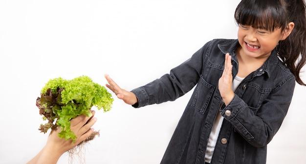 彼が好きではないグリーンサラダを保持しているアジアの女の子 Premium写真