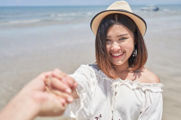 Asian girl holding hand of her boyfriend on the beach Premium Photo