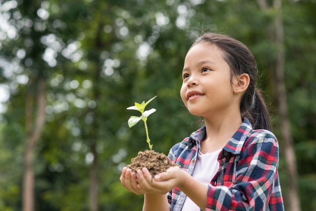 Asian girl holding plant and soil Free Photo