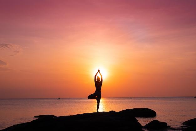 Asian girl practice yoga on the beach sunrise morning day Premium Photo