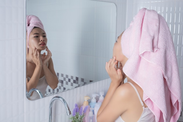 Asian girl squeezes acne. Free Photo