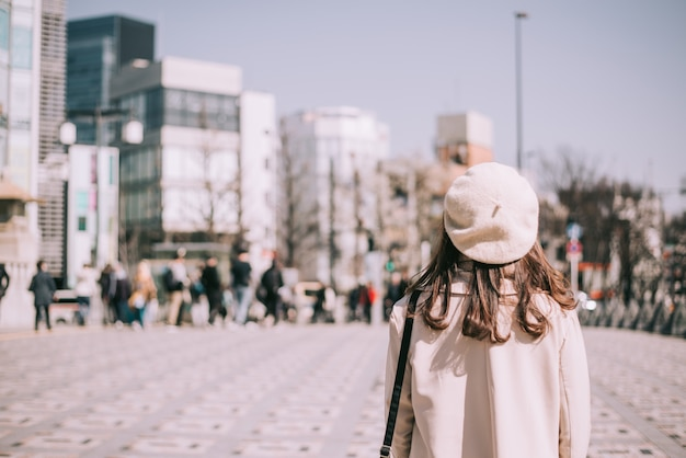 Asian girl standing out from the crowd at a city street in japan. Premium Photo