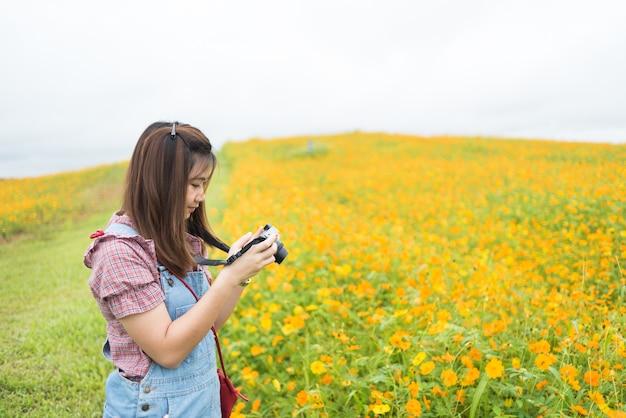Asian girl take photo blooming yellow flowers, travel concept Premium Photo