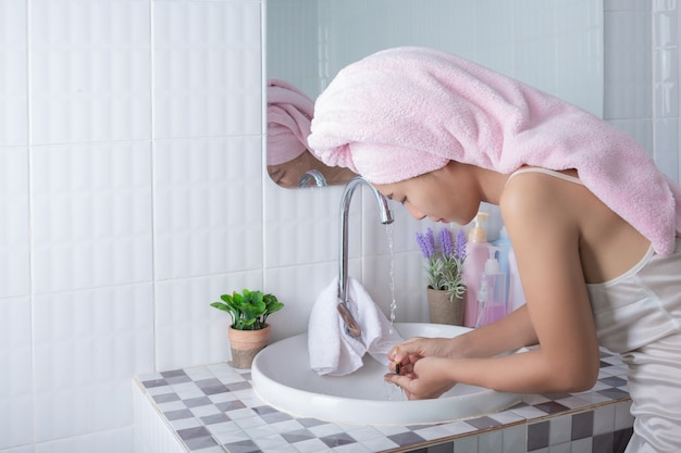 Asian girl washes face. Free Photo