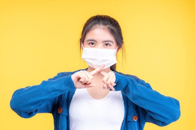 Ragazza asiatica che indossa la maschera per il viso mostra il gesto delle mani di arresto per arrestare lo scoppio del virus corona Foto Gratuite