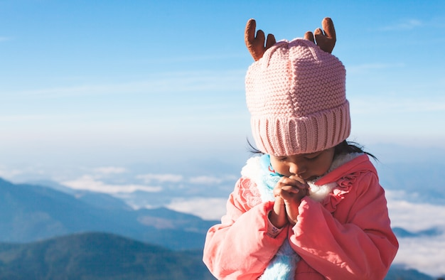 Asian girl wearing sweater and warm hat making folded hands in prayer Premium Photo