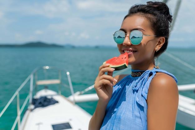 メガネのアジアの女の子は、ヨットでスイカを食べる。贅沢な旅行。夏休み。 Premium写真